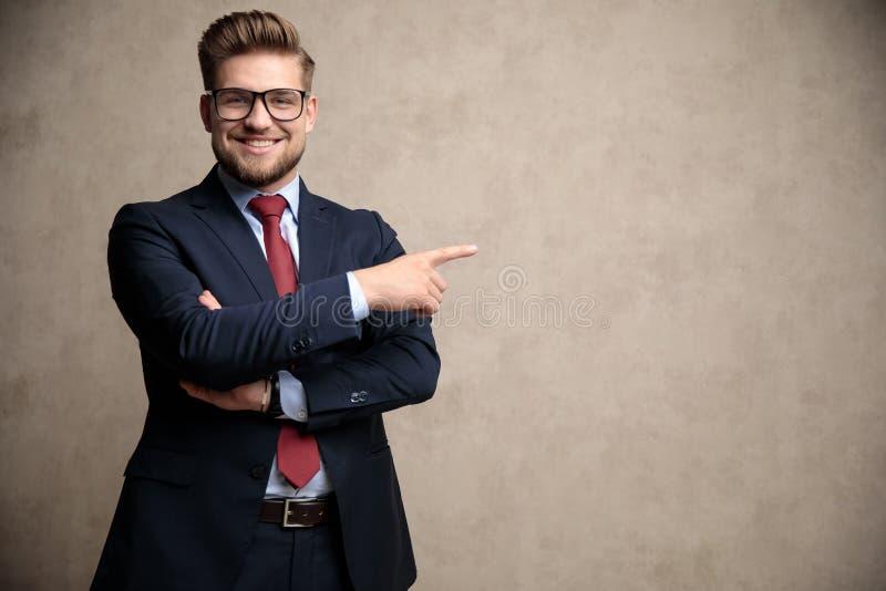 Homem de negócios positivo que aponta ao lado e ao sorriso imagem de stock