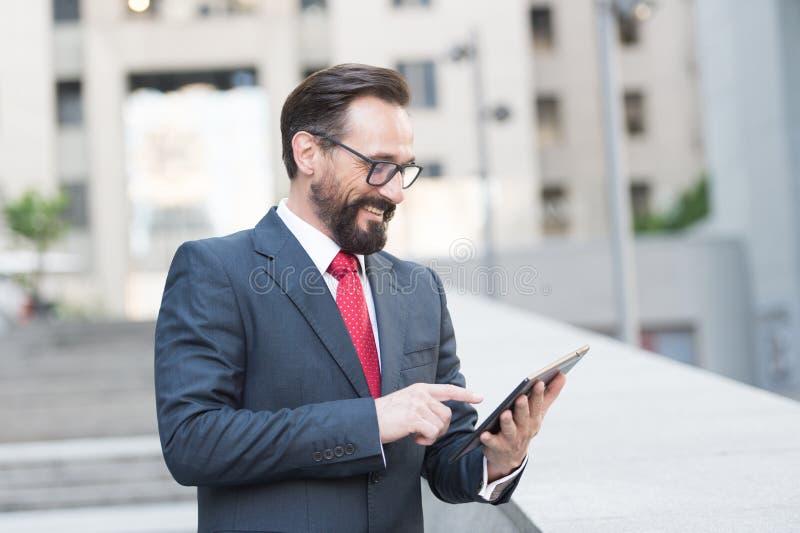 Homem de negócios positivo que usa uma tabuleta fora foto de stock