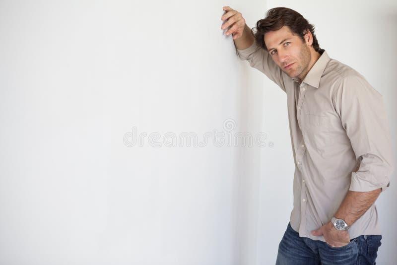 Homem de negócios preocupado ocasional que inclina-se na parede imagem de stock