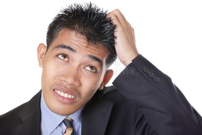 Homem de negócios preocupado que risca a cabeça imagens de stock