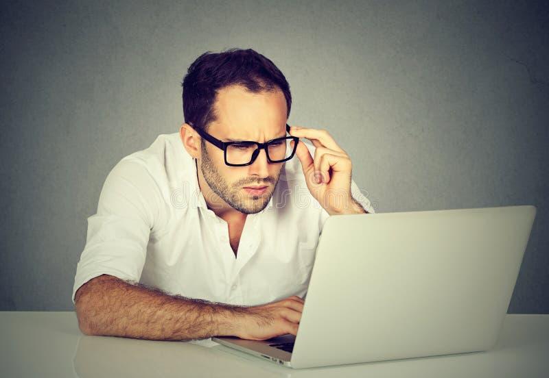 Homem de negócios preocupado que trabalha no laptop fotos de stock