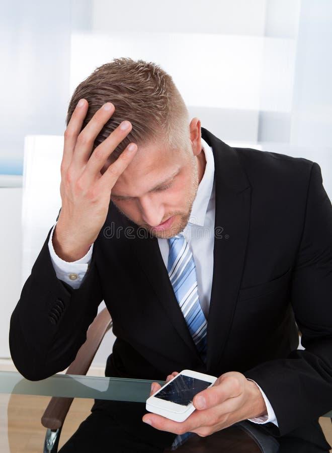 Homem de negócios preocupado que verifica uma mensagem móvel foto de stock royalty free