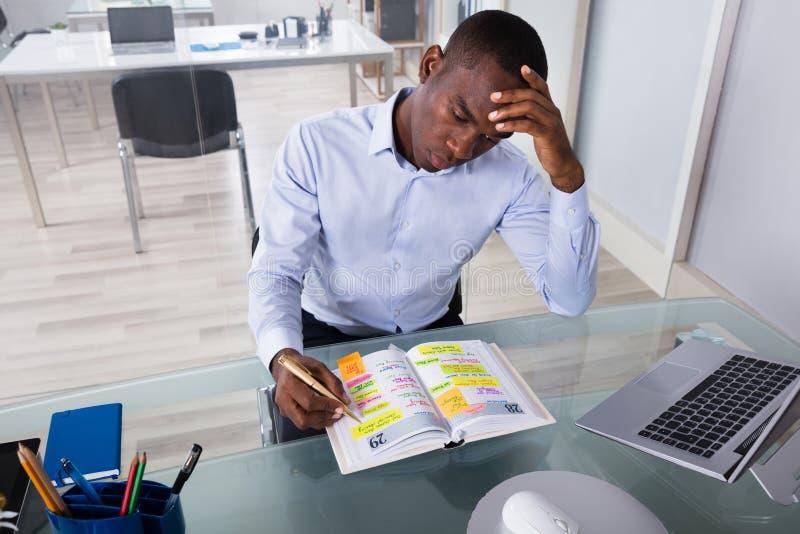 Homem de negócios preocupado Writing Schedule In o diário imagens de stock