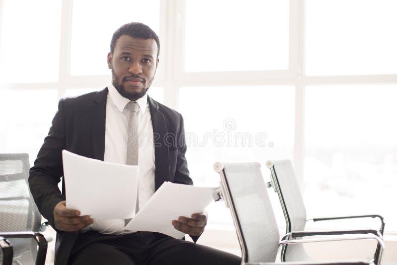 Homem de negócios preto com papéis imagem de stock royalty free