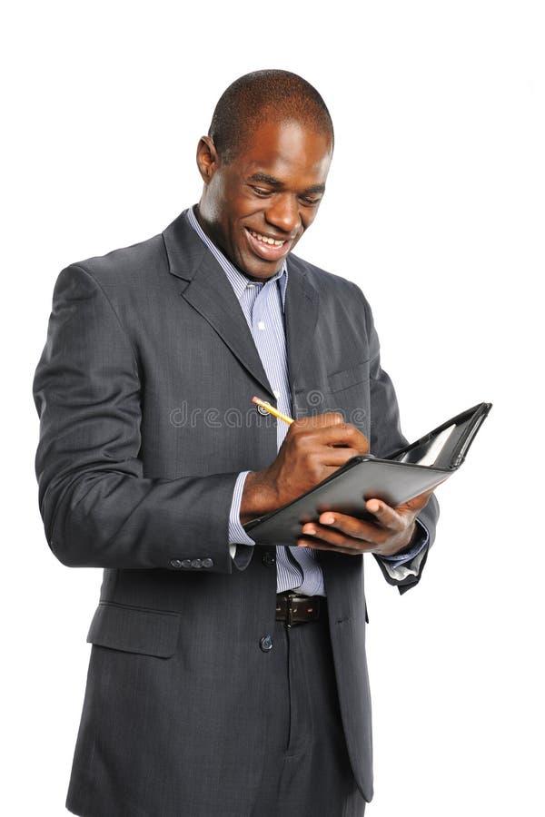 Homem de negócios preto de sorriso dos jovens que toma notas fotografia de stock royalty free