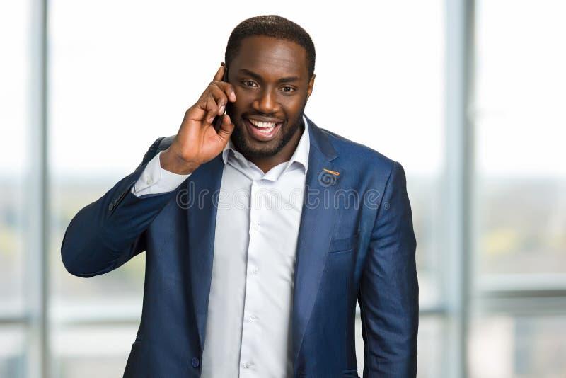 Homem de negócios preto feliz que faz uma chamada fotografia de stock royalty free