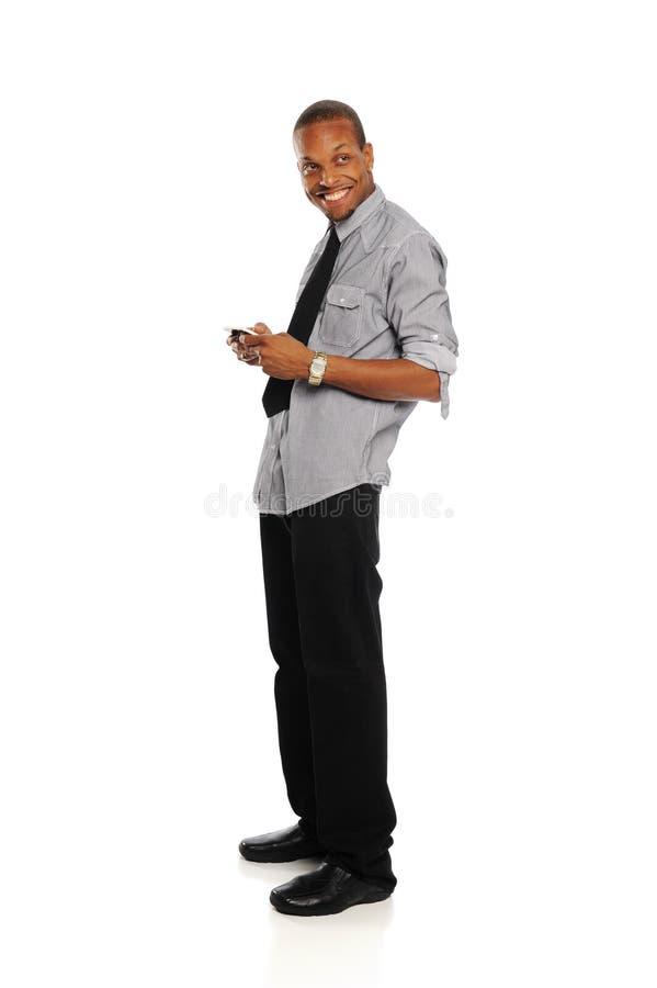 Homem de negócios preto novo com telefone esperto fotografia de stock
