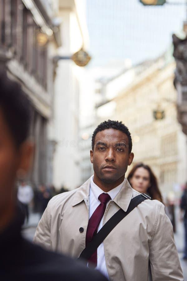 Homem de negócios preto novo que anda em anticipar ocupado da rua de Londres, fim acima, vertical fotos de stock