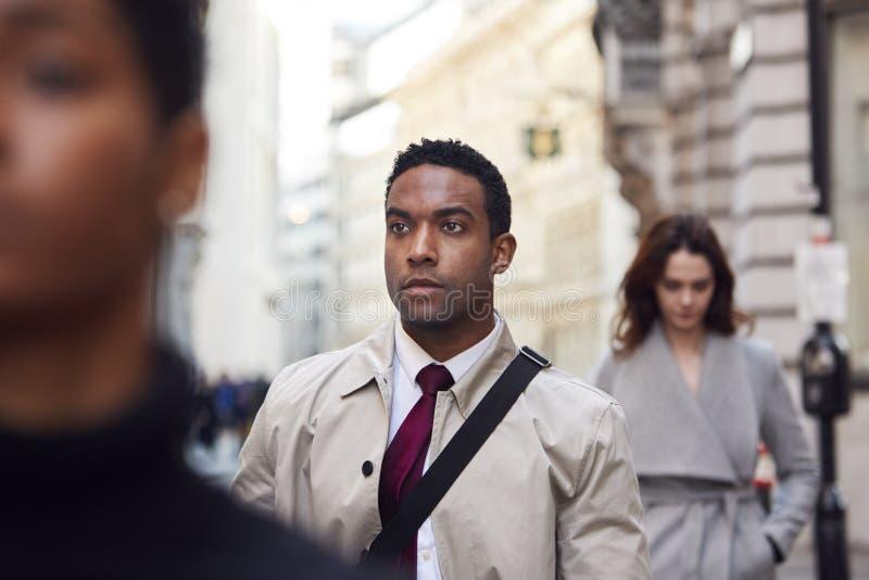 Homem de negócios preto novo que anda em uma rua ocupada de Londres que olha afastado, fim acima imagens de stock royalty free