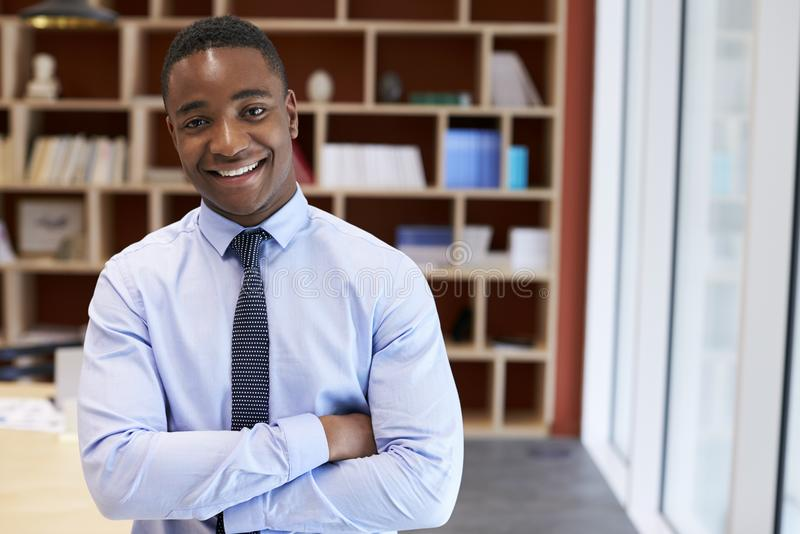 Homem de negócios preto novo que sorri à câmera em uma sala de reuniões foto de stock