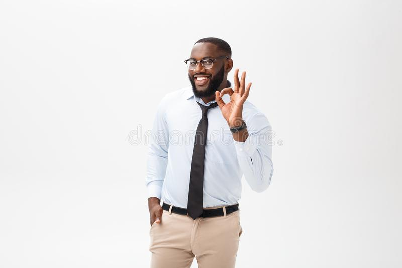 Homem de negócios preto novo que tem o olhar feliz, sorrindo, gesticular, mostrando o sinal APROVADO Aprovado-gesto mostrando mas imagens de stock royalty free