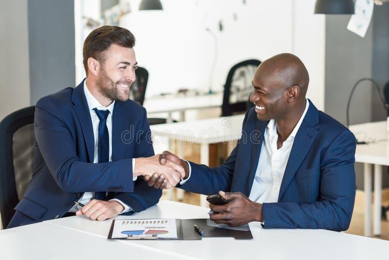Homem de negócios preto que agita as mãos com caucasiano no escritório fotos de stock
