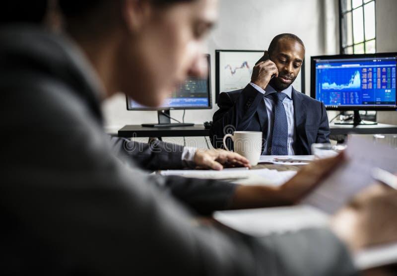 Homem de negócios preto que faz uma chamada na reunião de negócios fotos de stock
