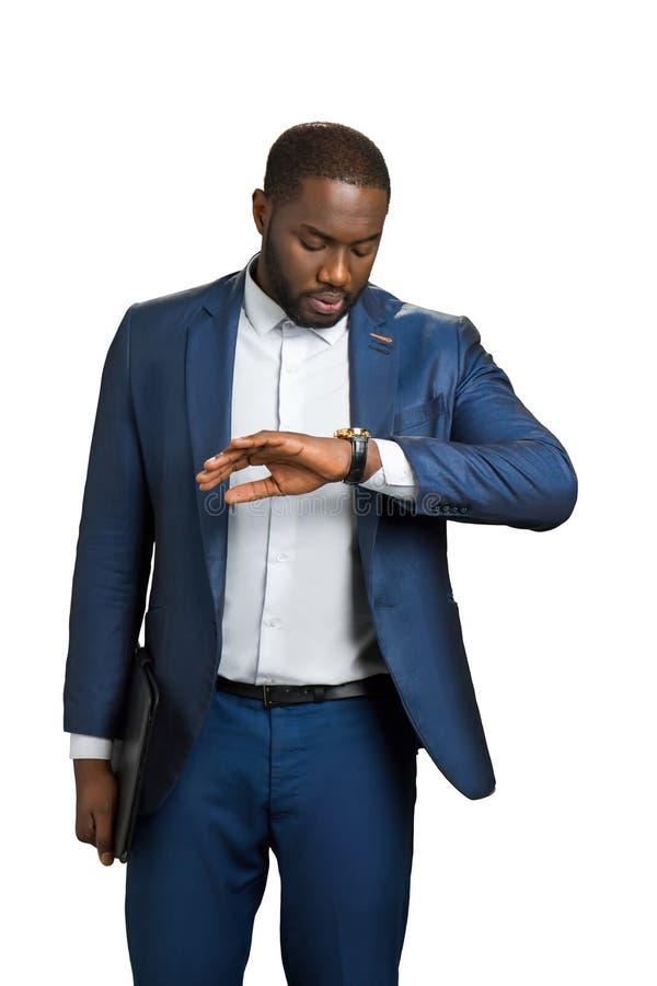 Homem de negócios preto que olha no relógio de pulso foto de stock