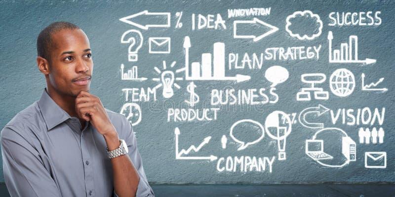 Homem de negócios preto que olha o esquema do negócio fotografia de stock
