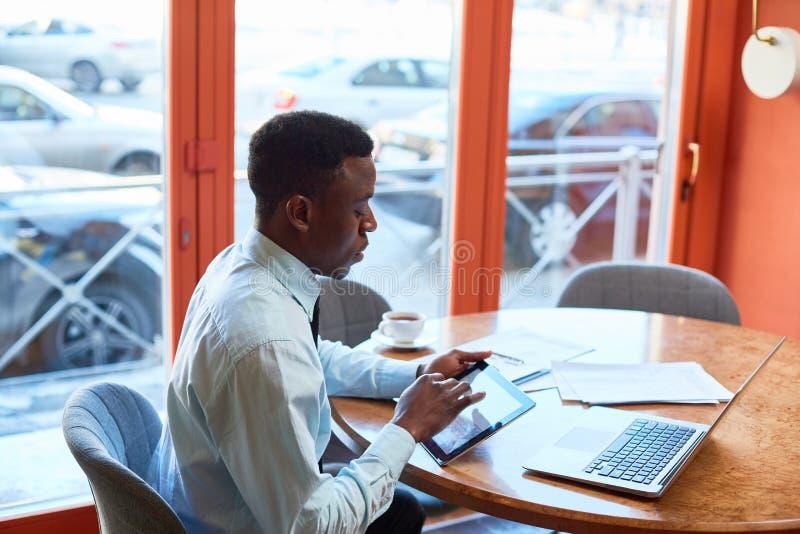 Homem de negócios preto que usa a tabuleta no café imagem de stock