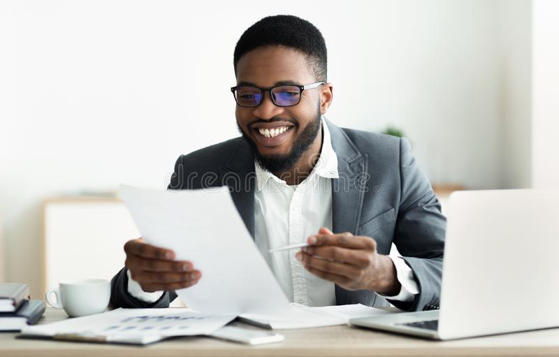 Homem de negócios preto de sorriso que verifica relatórios no escritório moderno fotografia de stock