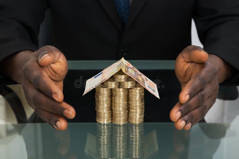 Homem de negócios Protecting House Made do dinheiro fotografia de stock royalty free