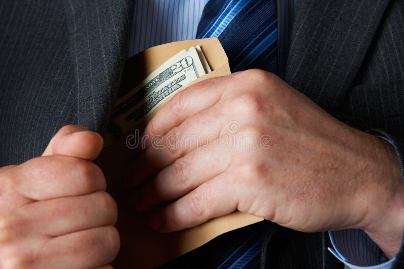 Homem de negócios Putting Envelope dos dólares no bolso fotografia de stock