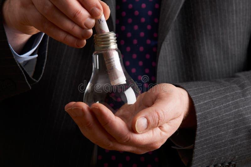 Homem de negócios Putting Sterling Note Into Light Bulb imagem de stock royalty free