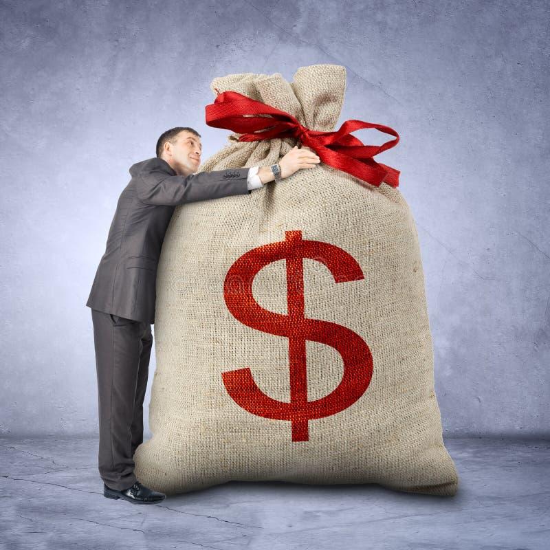 Homem de negócios que abraça o saco com sinal de dólar fotografia de stock royalty free