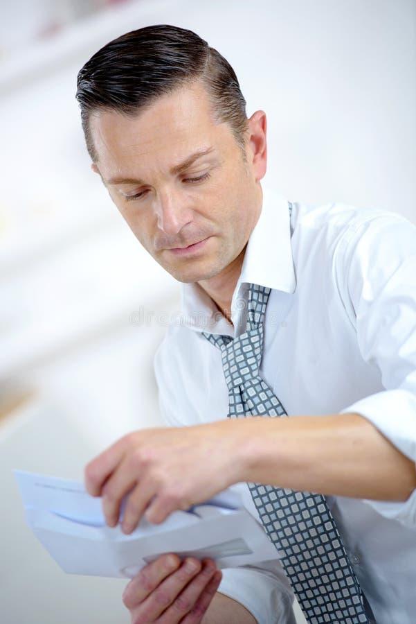 Homem de negócios que abre um envelope fotografia de stock