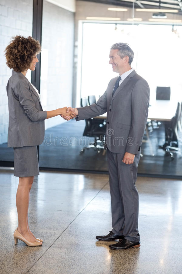 Homem de negócios que agita as mãos com mulher de negócios fotos de stock