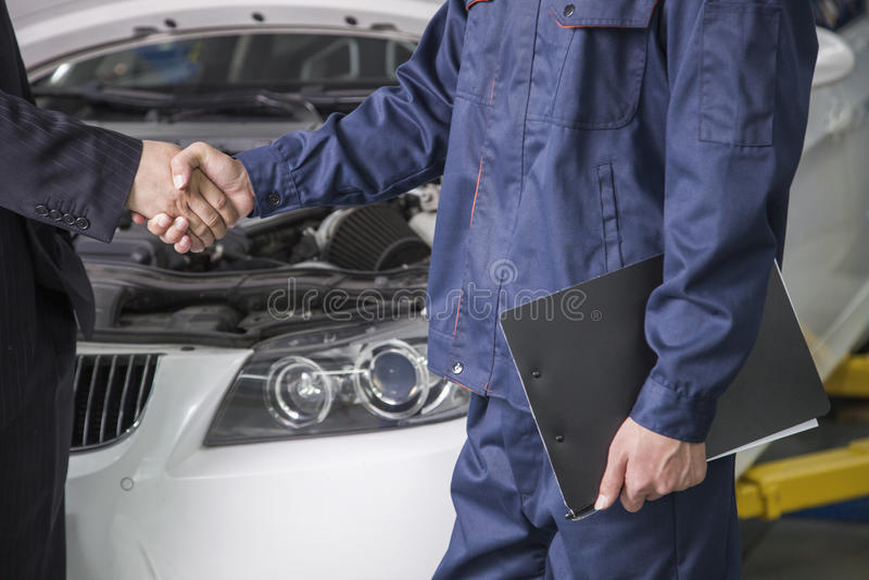Homem de negócios que agita as mãos com o mecânico na loja de reparação de automóveis imagem de stock