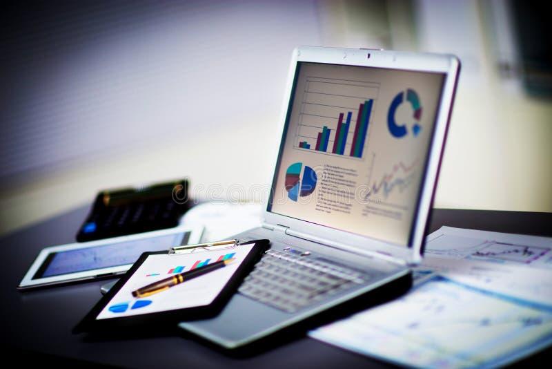 Homem de negócios que analisa cartas do investimento com portátil fotografia de stock royalty free