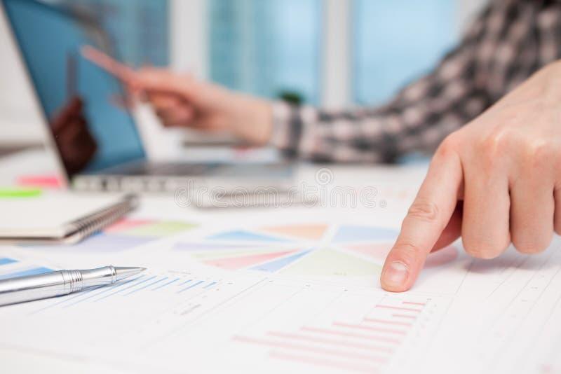 Homem de negócios que analisa gráficos e diagramas na tabela de madeira imagens de stock royalty free