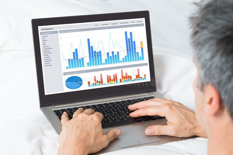 Homem de negócios que analisa gráficos em seu portátil foto de stock