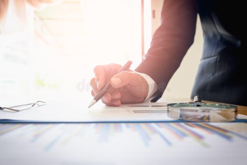 Homem de negócios que analisa o gráfico com folha da carta imagem de stock