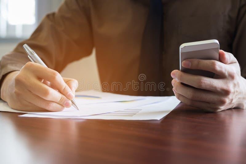 Homem de negócios que analisa o original do gráfico com portátil e que usa o telefone celular no escritório imagem de stock royalty free