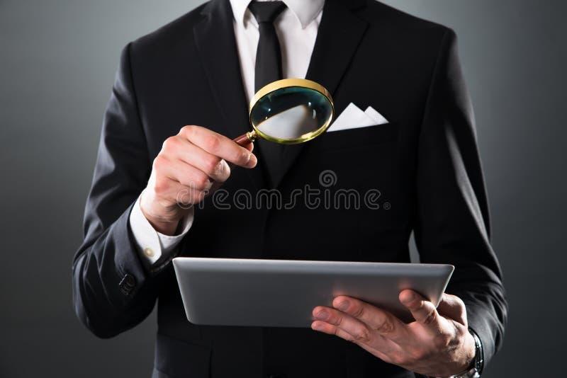 Homem de negócios que analisa a tabuleta digital com lupa imagens de stock royalty free