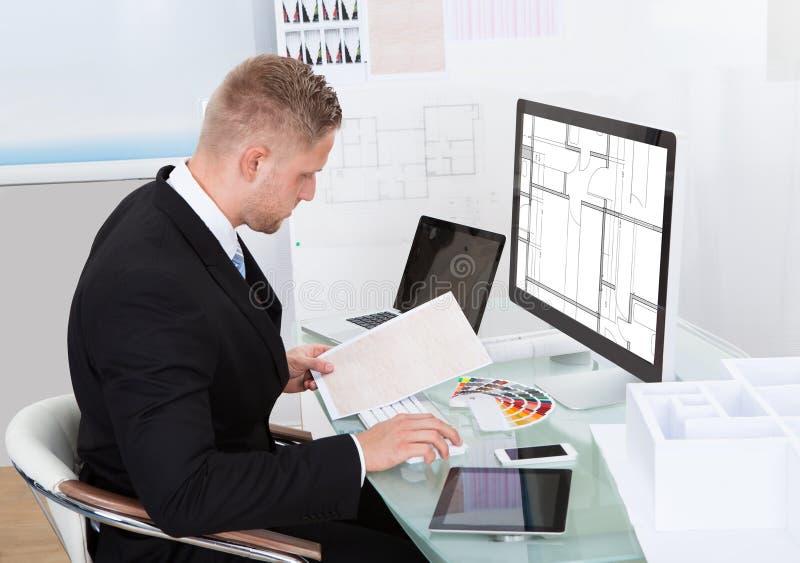 Homem de negócios que analisa uma verificação em linha da planilha fotos de stock