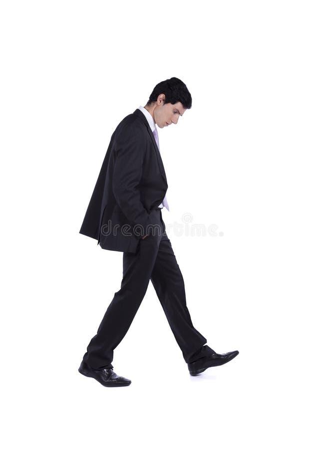 Homem de negócios que anda e que olha para baixo fotografia de stock