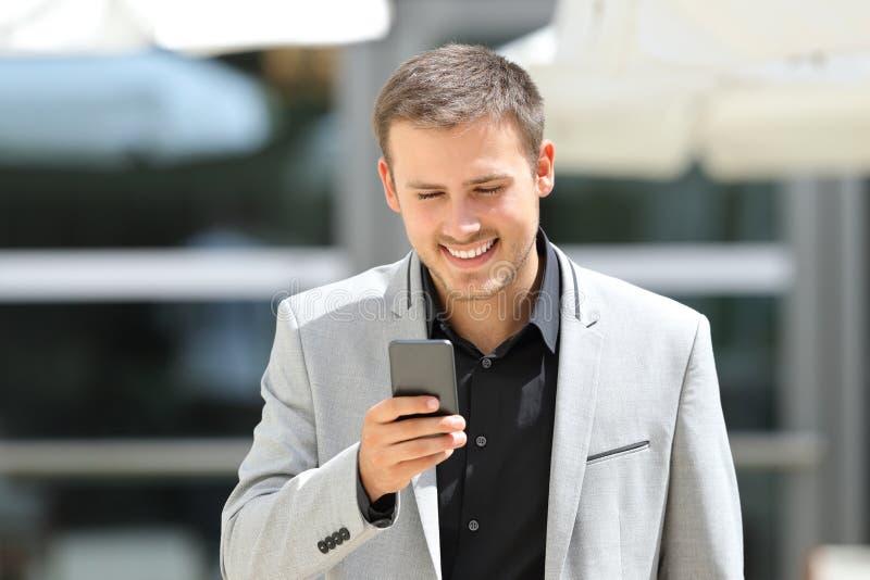 Homem de negócios que anda e que texting no telefone fotografia de stock royalty free