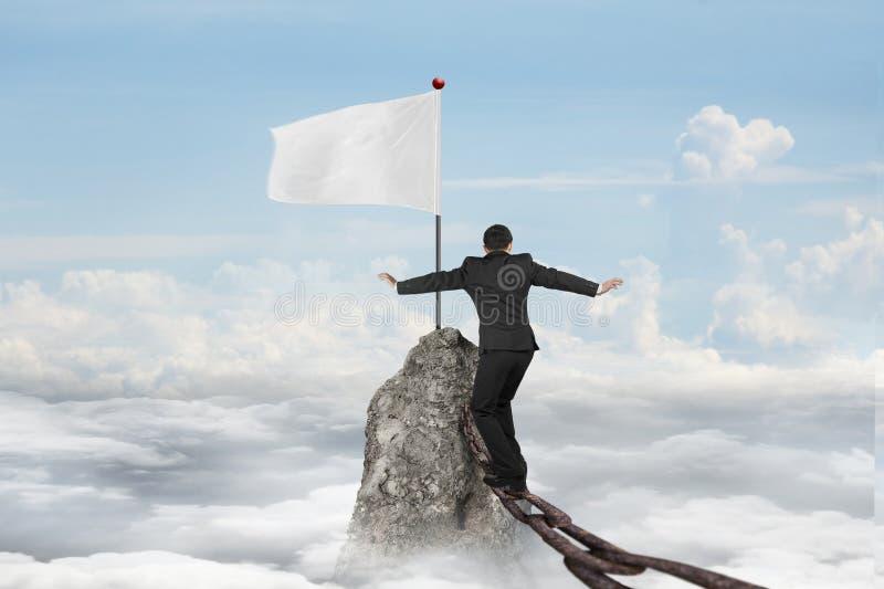Homem de negócios que anda na corrente do ferro para a bandeira branca com cloudsc fotografia de stock