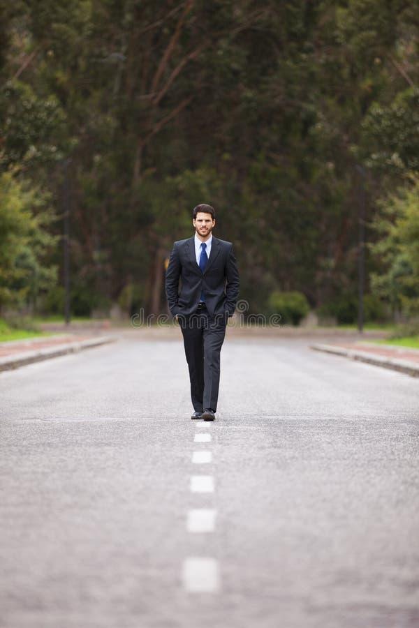 Homem de negócios que anda na estrada foto de stock royalty free