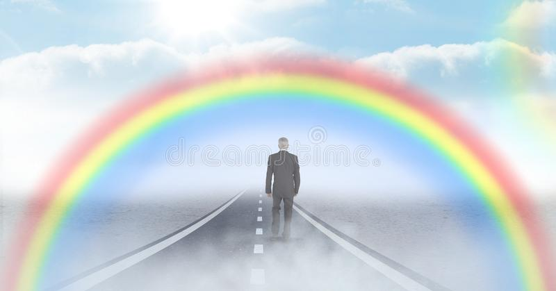 Homem de negócios que anda na estrada com arco-íris fotos de stock