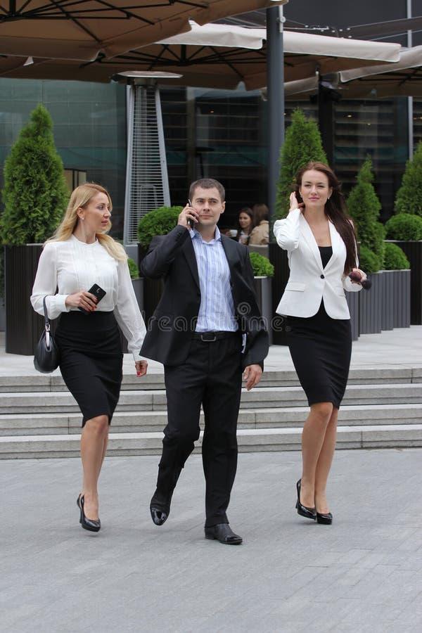 Homem de negócios que anda na rua com seus secretários imagens de stock