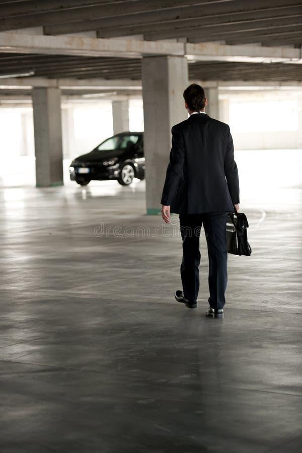 Homem de negócios que anda no estacionamento subterrâneo imagem de stock
