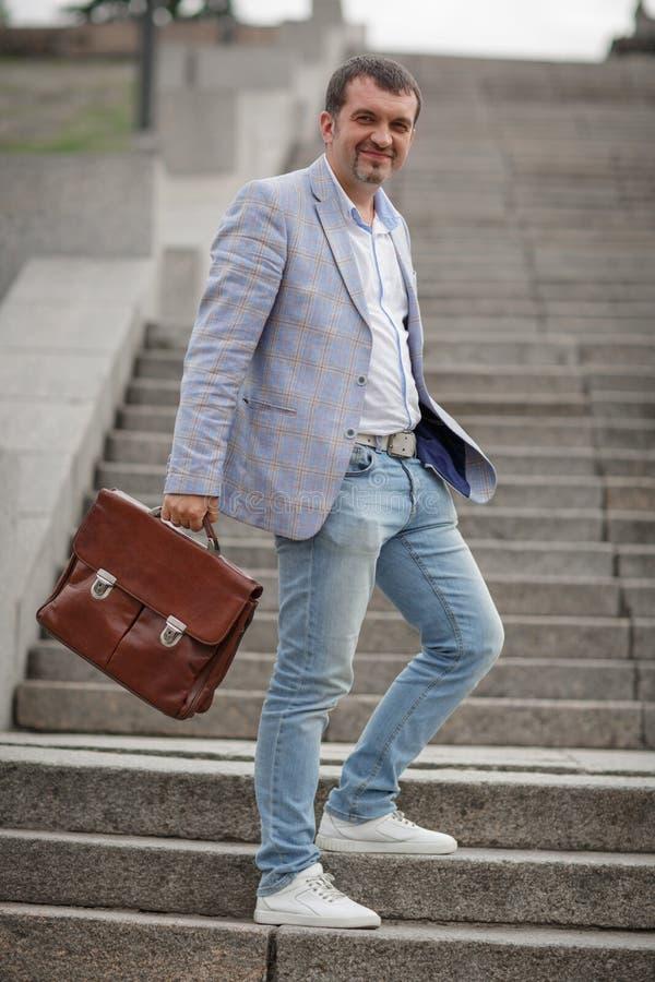 Homem de negócios que anda no fundo das escadas Homem de negócio em um terno elegante que guarda a pasta Conceito clássico do neg fotografia de stock