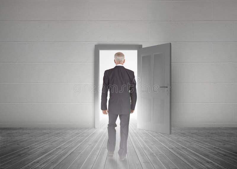 Homem de negócios que anda para a porta que mostra a luz fotografia de stock