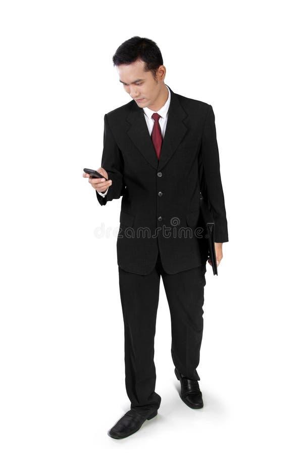 Homem de negócios que anda, verificando no telefone fotografia de stock