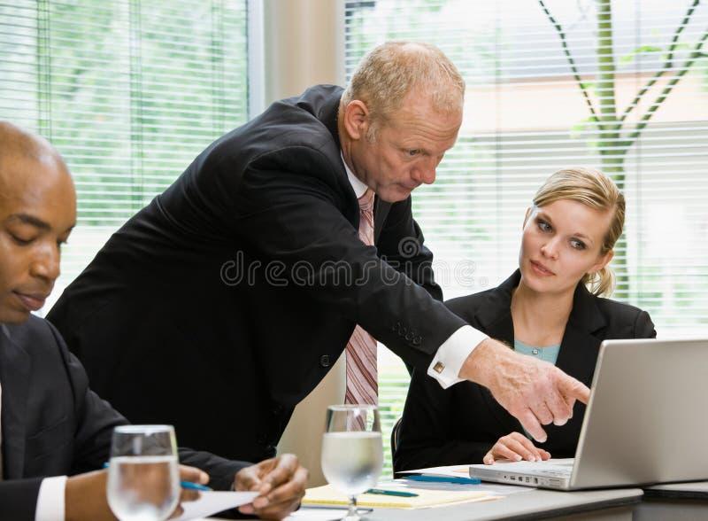 Homem de negócios que aponta ao portátil co-worker?s fêmea imagem de stock