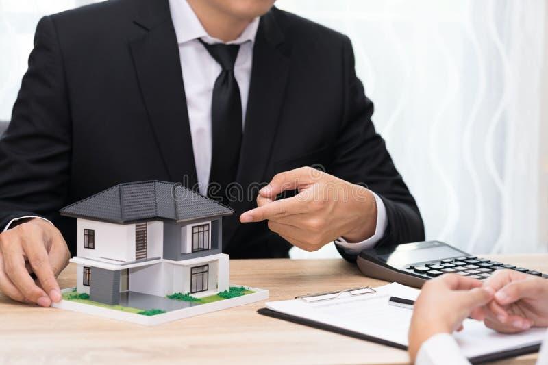 Homem de negócios que aponta e que apresenta em casa para a venda ao cliente imagens de stock