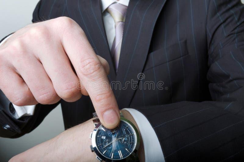 Homem de negócios que aponta em seu relógio imagens de stock royalty free