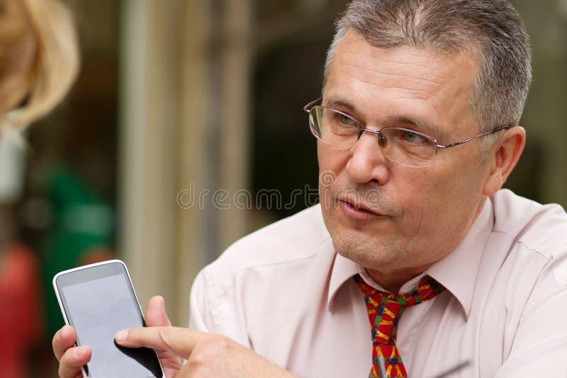 Homem de negócios que aponta em seu telefone esperto fotos de stock royalty free