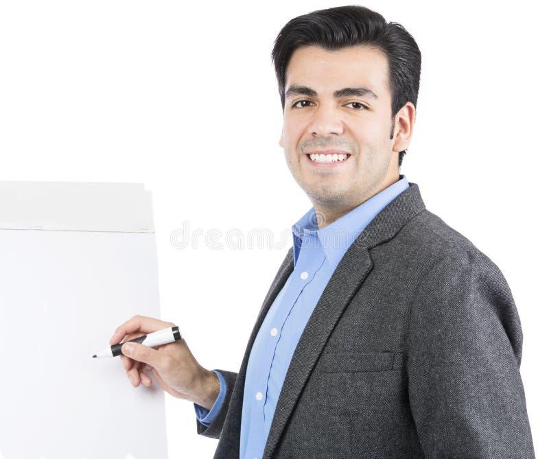 Homem de negócios que aponta no flipchart vazio branco foto de stock royalty free